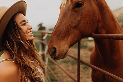 Young woman in felt hat face to face with horse, Jalama, California, USA - p924m2068261 by Peter Amend