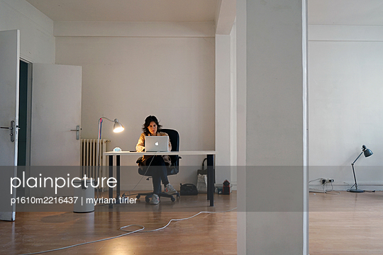 A woman working in an empty office - p1610m2216437 by myriam tirler