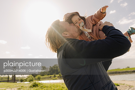 Father kissing baby daughter on cheek near river bank on sunny day - p300m2214006 by Gustafsson