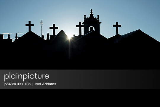 The sun peaks over a church and graveyard in Galicia, Spain on the Camino Primitivo, one route of the Camino de Santiago. - p343m1090108 by Joel Addams
