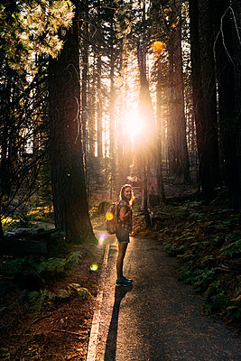 Woman with backpack hiking in the forest at sunset in Sequoia National Park, California, USA - p300m2140316 by Gemma Ferrando