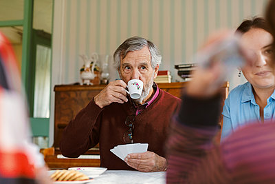 Senior man drinking coffee while playing cards with family at home - p426m1468277 by Maskot