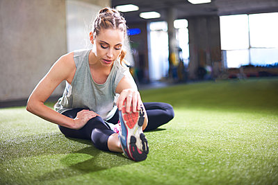 Woman doing stretching exercise in gym - p429m2019220 by Peter Muller