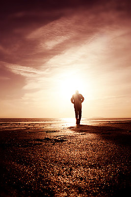 Silhouette man walking on beach with low sun - p597m2055250 by Tim Robinson