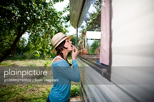 Young woman putting on lipstick at mobile home - p1093m2193602 by Sven Hagolani