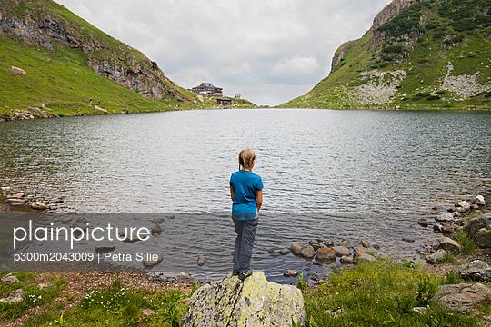 Austria, Tyrol, Fieberbrunn, Wildseeloder, girl standing at the shore of lake Wildsee - p300m2043009 von Petra Silie