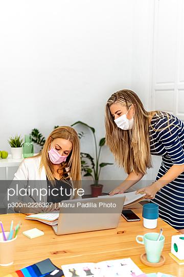 Business people wearing face mask working at office - p300m2226327 by Manu Padilla Photo