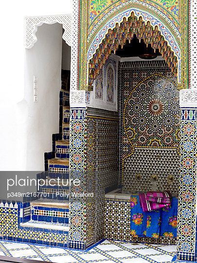 Fabrics in Moroccan courtyard with geometric tiling and recessed water basin, North Africa - p349m2167701 by Polly Wreford