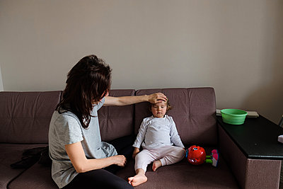 Woman checks her daughter's temperature - p1363m2177581 by Valery Skurydin