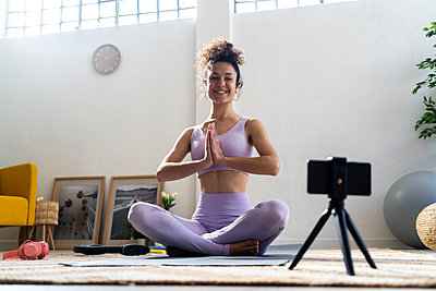 Smiling female influencer with hands clasped vlogging while doing yoga at home - p300m2274632 by Giorgio Fochesato