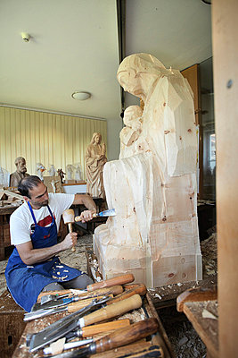 Sculptor chiseling figure from wood - p429m747165f by Stefano Gilera