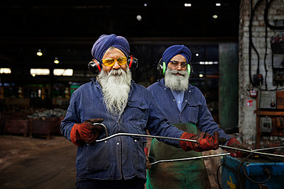 Forge workers pose whilst unloading forged components - p429m875674f by Charlie Fawell