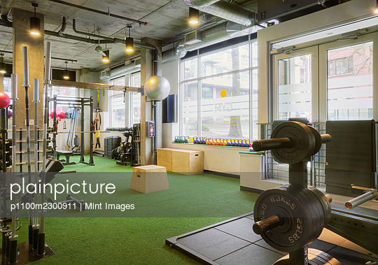 Weights room in an empty gym. - p1100m2300911 by Mint Images