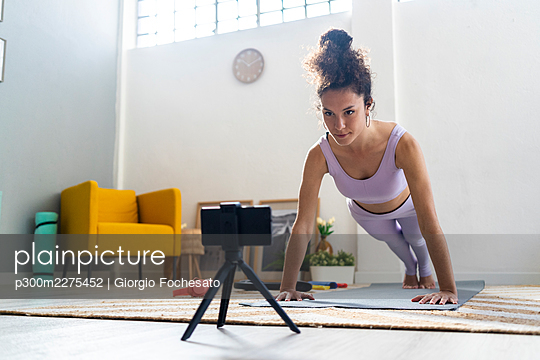 Female influencer doing push-ups while filming through mobile phone at home - p300m2275452 by Giorgio Fochesato