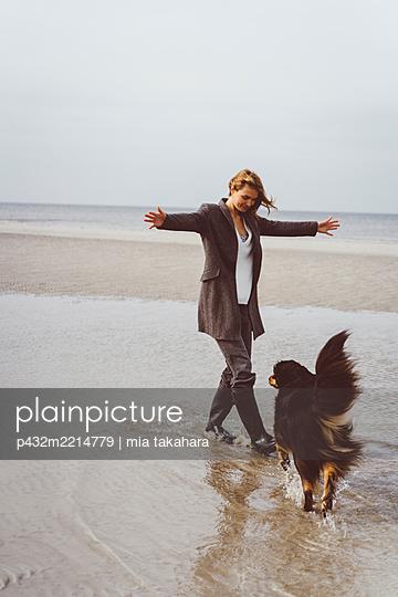 Junge Frau genießt die Zeit mit ihrem Hund am Meer - p432m2214779 von mia takahara