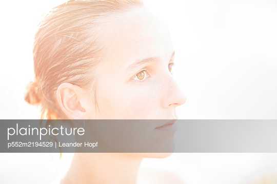Portrait of young woman against the light - p552m2194529 by Leander Hopf