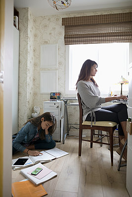 Tween daughter studying on floor behind mother working in home office - p1192m2000296 by Hero Images