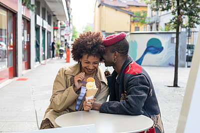 Couple enjoying ice-cream at sidewalk cafe, Milan, Italy - p429m2127805 by Garage Island Crew