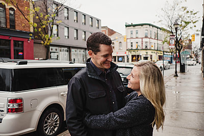 Mid adult couple hugging in street, smiling - p924m1557790 by Jennifer van Son