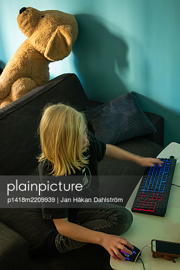 Teddy bear and boy playing computer game - p1418m2209939 by Jan Håkan Dahlström