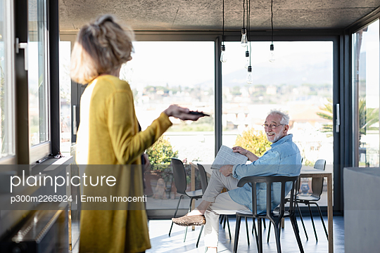Smiling man looking at woman while sitting on chair at home - p300m2265924 by Emma Innocenti