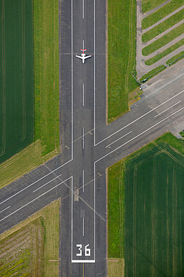 Aerial view of airport runway with private jet - p1048m2088023 by Mark Wagner