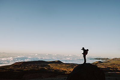 Silhouette of a male hiker pointing at volcanic landscape - p1166m2124322 by Cavan Images