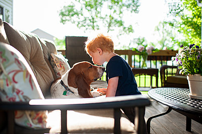Toddler boy kissing his basset hound dog on the deck in spring - p1166m2146864 by Cavan Images