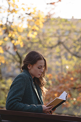 Young woman reading a book in the park - p1315m1566532 by Wavebreak