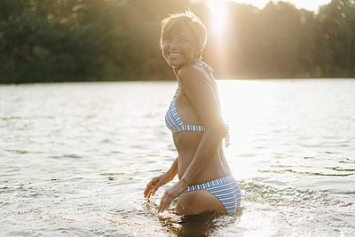 Portrait of happy woman wearing a bikini in a lake - p300m2059038 von Kniel Synnatzschke