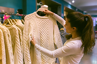 Woman holding a pullover in a vintage boutique - p300m2104073 by Marco Govel