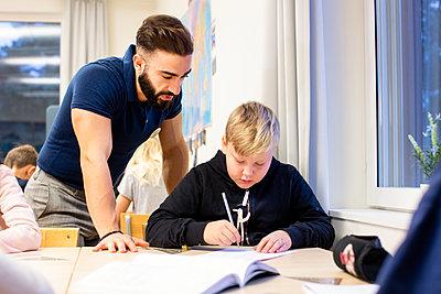 Teacher with schoolboy in classroom - p312m2174781 by Scandinav