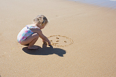 Little girl drawing smiley face in sand - p623m1221312 by Anne-Sophie Bost