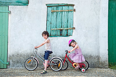 Young brother and sister riding bicycles together - p675m922771 by Jerome Gorin