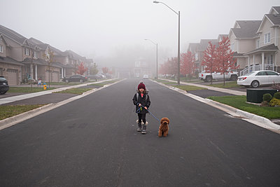 Girl walking dog in middle of misty suburban road, full length portrait - p924m2135693 by Kymberlie Dozois Photography