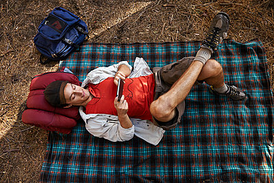 Overhead view of young male camper lying on picnic blanket in forest, Los Angeles, California, USA - p924m998769f by Tony Garcia