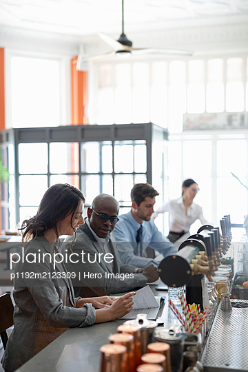Business colleagues enjoying working lunch in bar - p1192m2123309 by Hero Images
