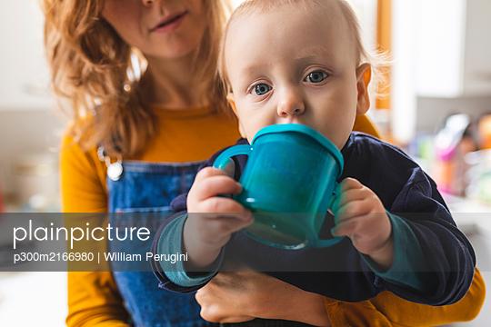Portrait of drinking baby boy being held by his mother - p300m2166980 von William Perugini