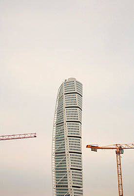 High section of the Turning Torso and cranes against clear sky at Malmo, Sweden - p1025m788908f by Pär Lindblad