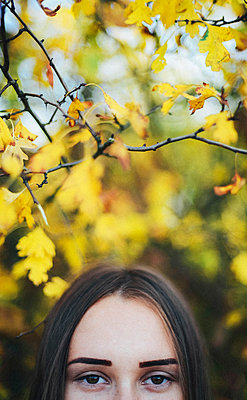 Cropped portrait of woman by trees at park during autumn - p1166m1546267 by Cavan Social