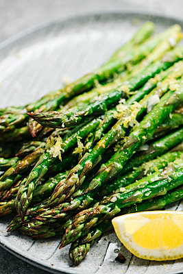Close up of lemon garlic asparagus tips - p1166m2162859 by Cavan Images