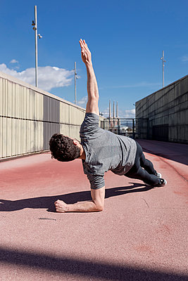 Sportive man exercising outdoors between walls - p300m2005496 von Mauro Grigollo