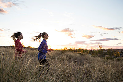 Young women running together through a meadow at sunrise - p300m2131659 by Andrés Benitez