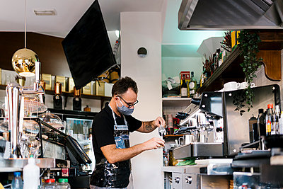 Male barista wearing protective face mask while working in cafe during COVID-19 crisis - p300m2220710 by Ezequiel Giménez