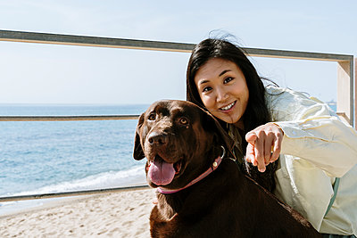 Beautiful woman with Labrador dog pointing on sunny day at beach - p300m2281340 by VITTA GALLERY