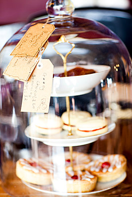 Home made cakes for sale under a glass cloche on tea room counter - p429m1477737 by JAG IMAGES