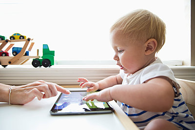 Caucasian mother helping baby girl use digital tablet - p555m1305160 by Jasper Cole