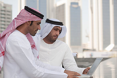 Middle eastern businessmen using laptop outdoors - p9244774f by Image Source