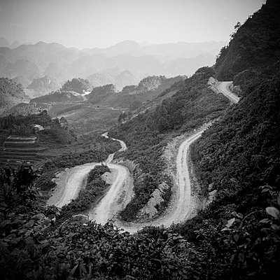 A long winding road cuts through the vast mountainous landscape of Ha Giang Province in Northern Vietnam, Southeast Asia - p934m893014 by Aaron Joel Santos
