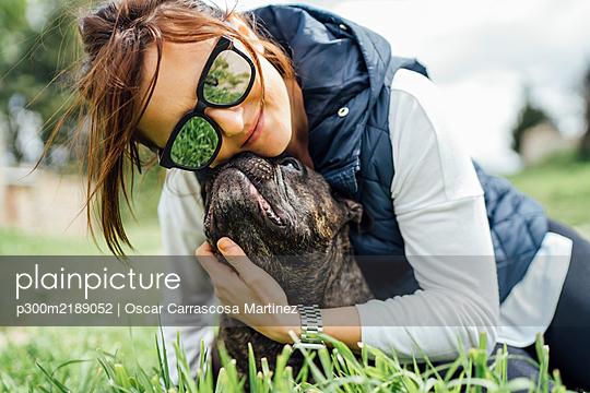 Portrait of happy woman cuddling her bulldog on a meadow - p300m2189052 by Oscar Carrascosa Martinez